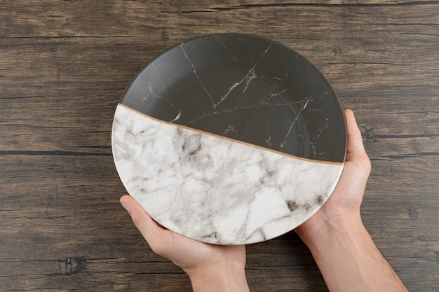 Vista superior das mãos do homem segurando um lindo prato vazio sobre uma mesa de madeira.