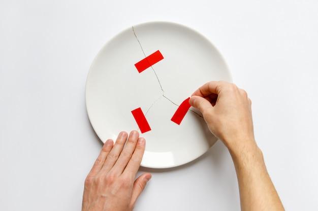 Vista superior das mãos do homem segurando um prato branco quebrado, colas de peças com fita vermelha