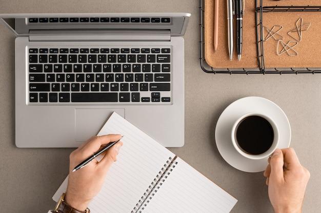 Vista superior das mãos do jovem empresário com uma xícara de café para escrever o plano de trabalho na página em branco do caderno pela manhã