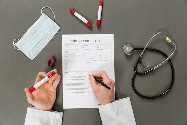 Vista superior das mãos do médico preenchendo um teste de coronavírus