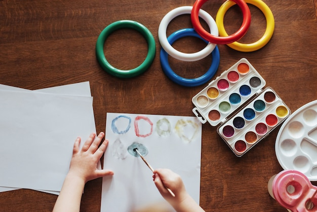 Vista superior das mãos e pincel guache aquarela de tinta