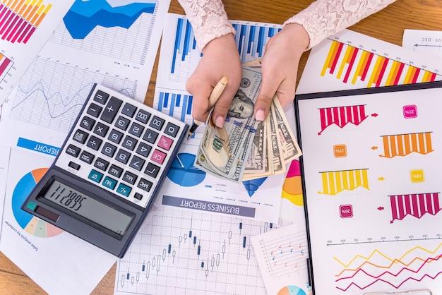 Vista superior das mãos femininas com dólares e gráficos de negócios