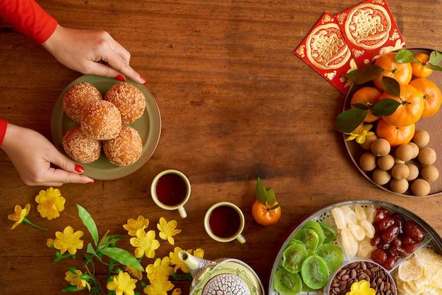 Vista superior das mãos femininas cortadas, servindo pratos, preparando-se para a celebração do ano novo
