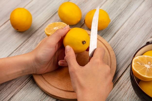 Vista superior das mãos femininas cortando limão fresco em uma placa de cozinha de madeira com uma faca com limões em uma tigela com limões isolados em um fundo cinza de madeira