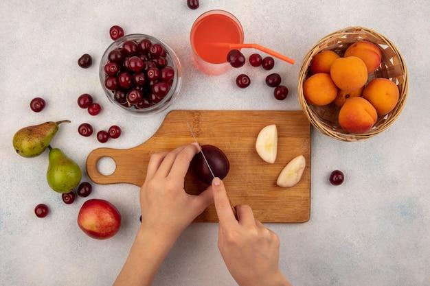 Vista superior das mãos femininas cortando pêssego com faca na tábua e suco de cereja com pote de cereja e cesta de damasco com peras no fundo branco