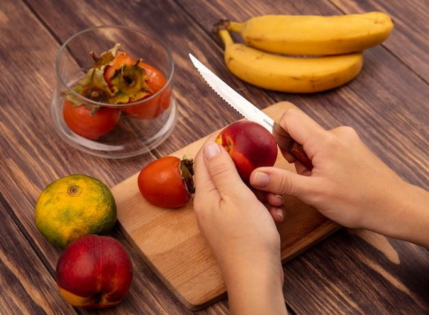 Vista superior das mãos femininas cortando um pêssego suculento em uma placa de cozinha de madeira com uma faca com tangerina e bananas isoladas em uma parede de madeira