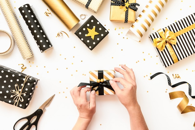 Vista superior das mãos femininas, embrulho de caixas de presente, materiais de embrulho espalhados em vários preto, branco e dourado