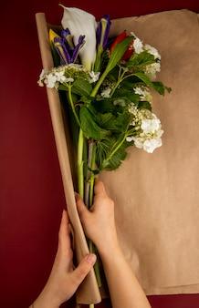 Vista superior das mãos femininas, envolvendo um buquê de lírio de calla viburno florescendo e flores de íris roxo escuro com papel ofício na mesa vermelha escura