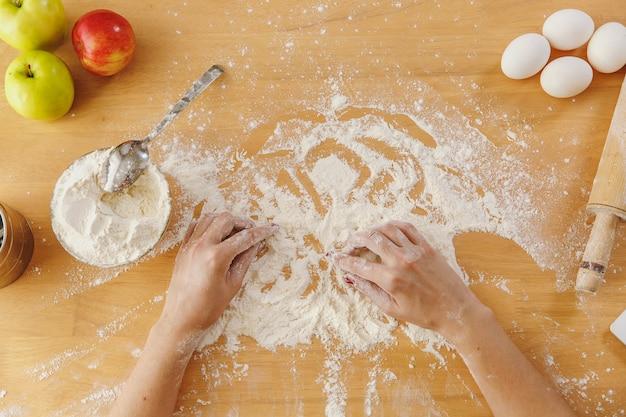 Vista superior das mãos femininas, farinha e outros ingredientes na mesa da cozinha