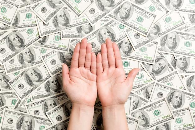 Vista superior das mãos femininas no fundo do dólar. conceito de riqueza com espaço vazio para seu projeto. conceito de dinheiro implorando.