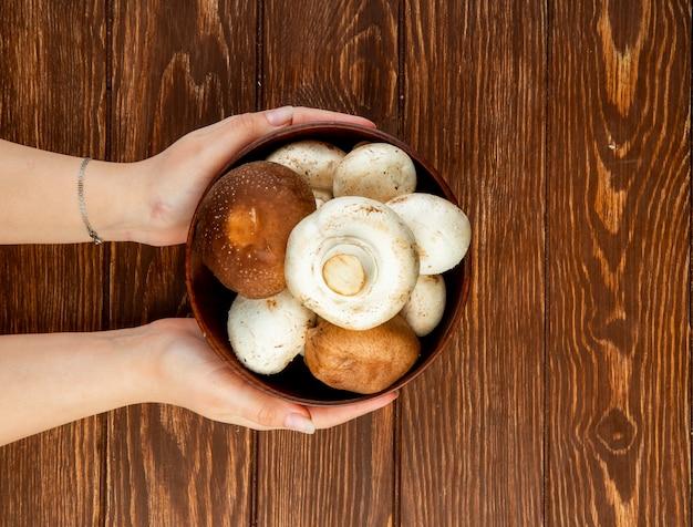 Vista superior das mãos femininas segurando cogumelos frescos em uma tigela de madeira rústica
