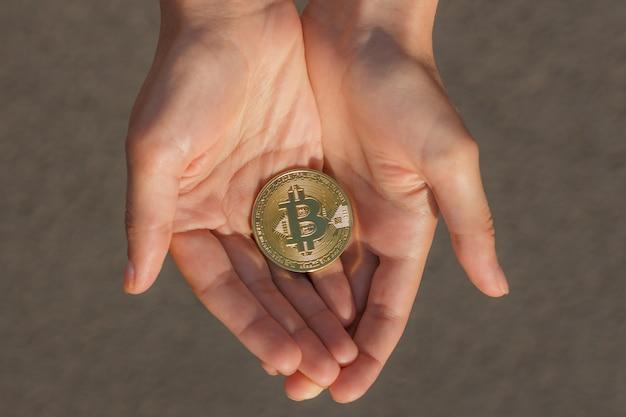 Vista superior das mãos femininas segurando muitas moedas de bitcoin em um asfalto cinza nos raios de sol.