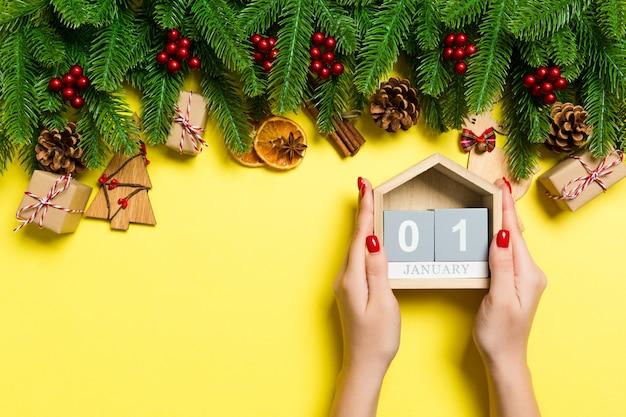Vista superior das mãos femininas segurando o calendário em amarelo.