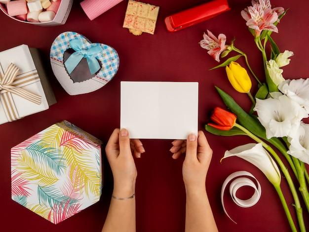 Vista superior das mãos femininas segurando o cartão de papel em branco sobre a mesa vermelha com tulipas de cores vermelhas e amarelas com alstroemeria e caixa de presente em forma de coração e chocolate branco