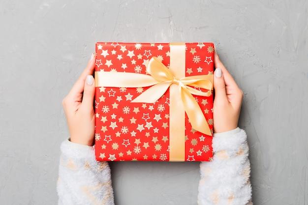 Vista superior das mãos femininas segurando o natal ou outro pacote de caixa de presente artesanal de férias nas palmas, plana leigos