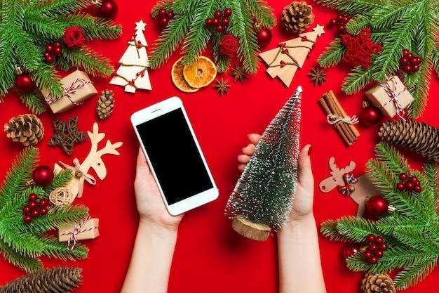 Vista superior das mãos femininas, segurando o telefone em uma mão e a árvore de natal em outra mão. conceito de feriado de ano novo.