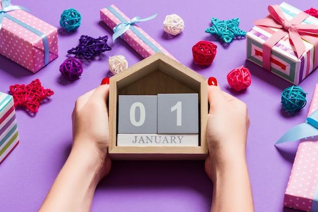 Vista superior das mãos femininas segurando um calendário em fundo roxo. o primeiro de janeiro. decorações de férias. conceito de ano novo.
