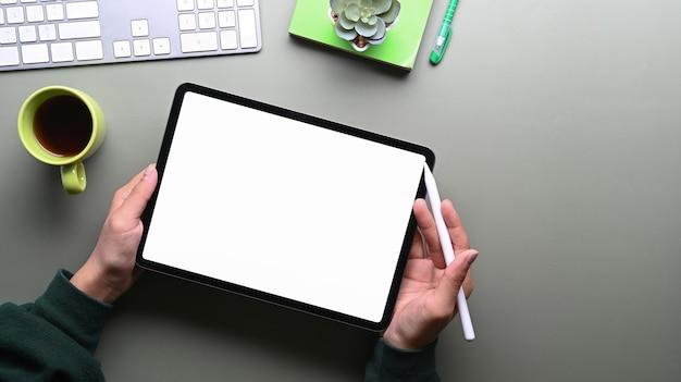 Vista superior das mãos femininas segurando um tablet digital e uma caneta stylus com tela em branco na mesa verde. tela em branco para mensagem de texto ou conteúdo de informação.