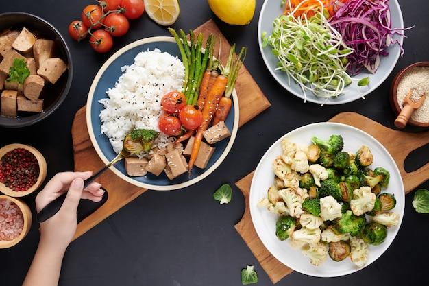 Vista superior das mãos femininas segurando uma tigela com salada de legumes, jovem comendo salada fresca vegetariana.