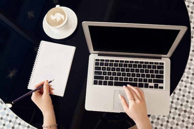 Vista superior das mãos femininas, trabalhando no laptop com tela preta em branco