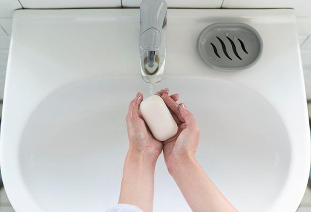 Vista superior das mãos lavando na pia com barra de sabão