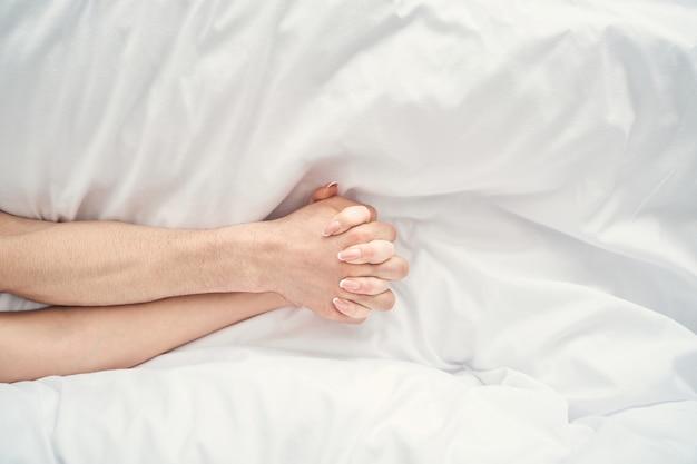 Vista superior das mãos masculina e feminina com dedos entrelaçados deitada na cama