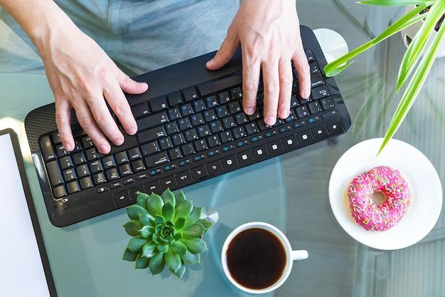 Vista superior das mãos masculinas em um teclado de computador.