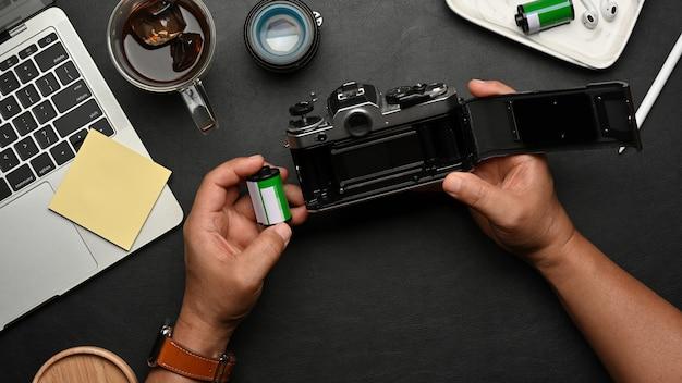 Vista superior das mãos masculinas usando a câmera de filme na mesa preta com suprimentos e acessórios