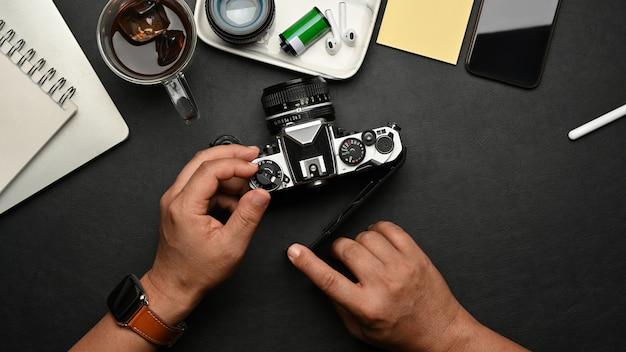 Vista superior das mãos masculinas usando a câmera na mesa preta com suprimentos e acessórios