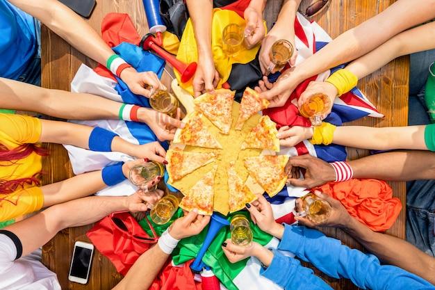 Vista superior das mãos multiétnicas de torcedor de esporte futebol compartilhando pizza margherita
