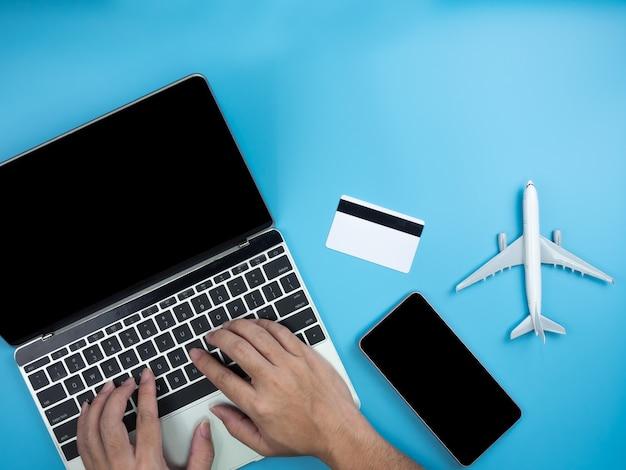 Vista superior das mãos no laptop, smartphone, cartão de crédito e avião