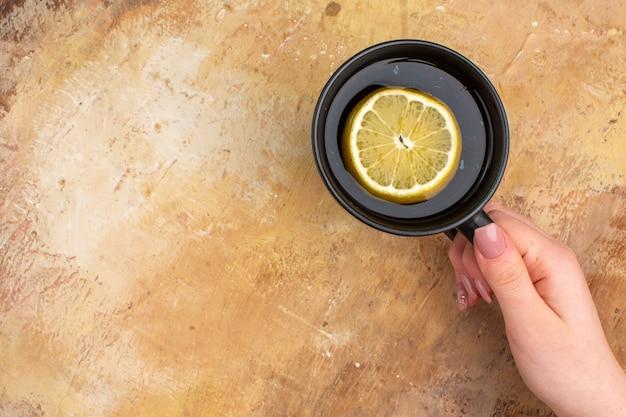 Vista superior das mãos segurando chá preto em uma xícara com limão em fundo de cor mista