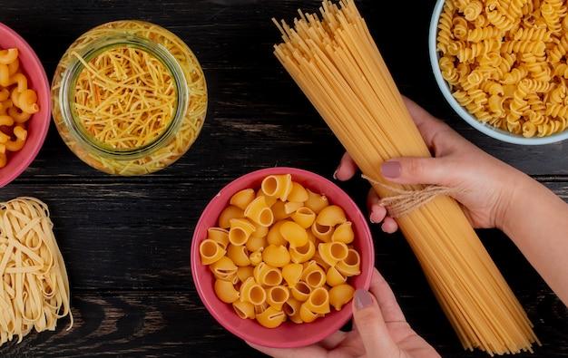Vista superior das mãos segurando macarrão aletria com diferentes tipos de macarrão como cavatappi rotini tagliatelle e espaguete na superfície de madeira