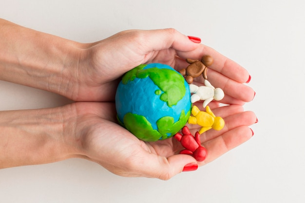 Vista superior das mãos segurando pessoas e globo de plasticina