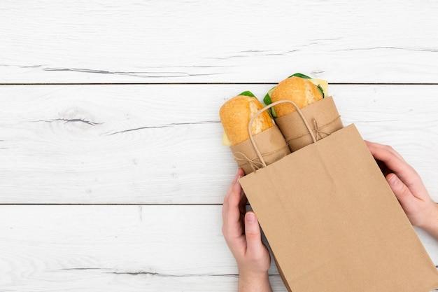Vista superior das mãos segurando sanduíches em saco de papel