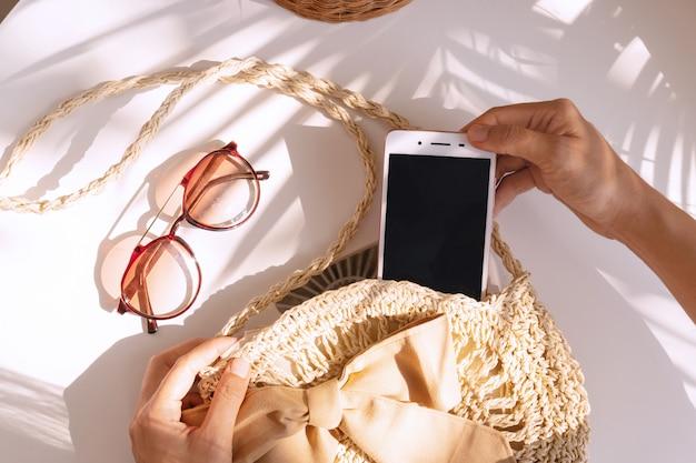 Vista superior das mãos segurando telefone inteligente, saco de verão e óculos de sol sobre fundo de cor branca, conceito de viagens.