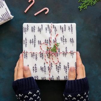 Vista superior das mãos segurando um presente de natal lindamente decorado
