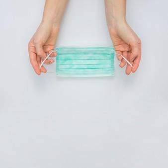 Vista superior das mãos segurando uma máscara médica com espaço de cópia