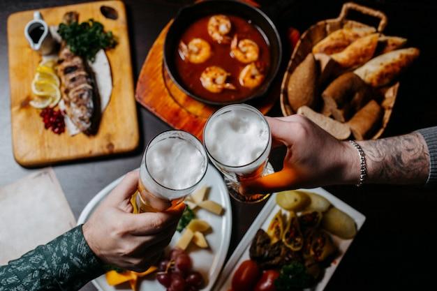 Vista superior das mãos segurando uma superfície de pub de copos de cerveja