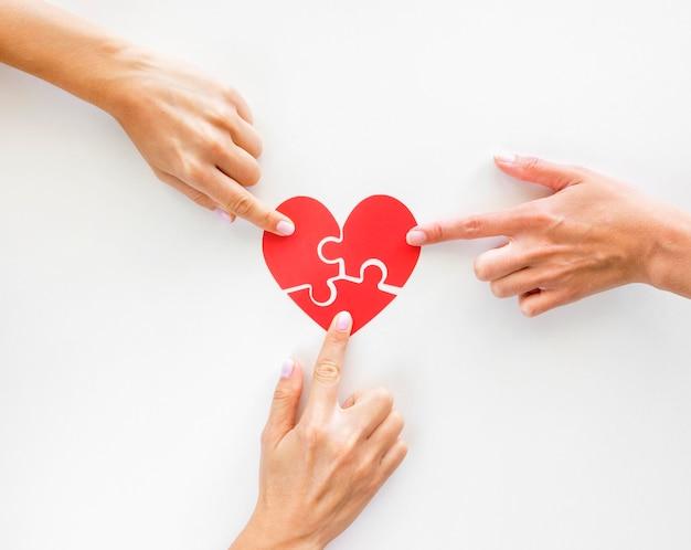 Vista superior das mãos tocando peças de coração de quebra-cabeça