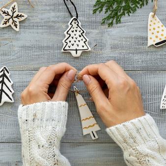 Vista superior das mãos trabalhando na decoração da árvore de natal
