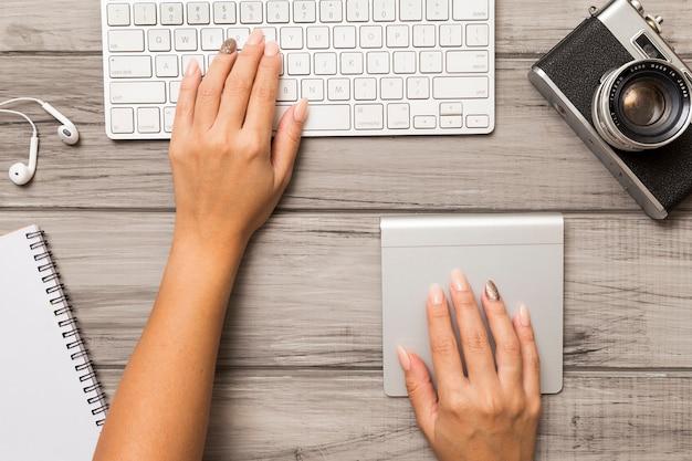 Vista superior das mãos trabalhando no computador na área de trabalho com câmera fotográfica