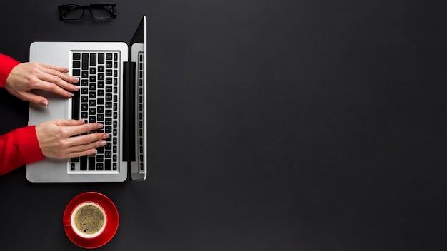 Vista superior das mãos trabalhando no laptop com espaço para café e cópia