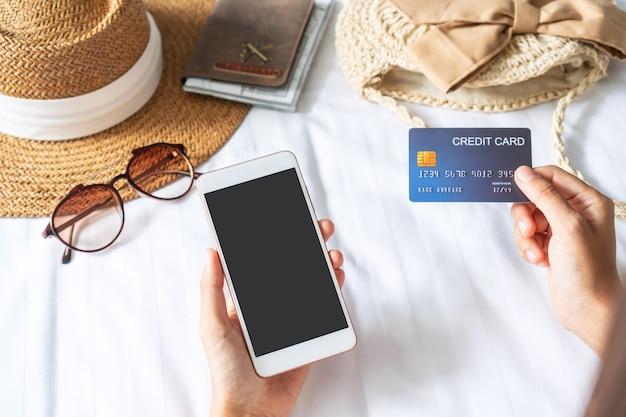 Vista superior das mãos usando telefone celular e cartão de crédito