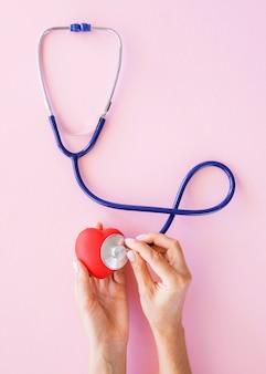 Vista superior das mãos verificando o coração com estetoscópio