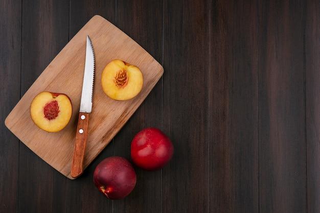 Vista superior das metades de pêssegos em um quadro negro com uma faca em uma superfície de madeira