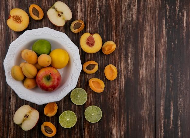 Vista superior das metades de uma mistura de frutas damascos maçãs pêssego e limão em uma superfície de madeira