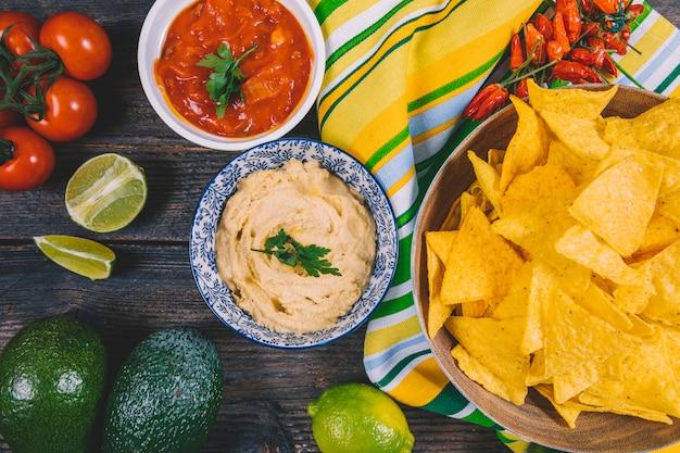 Vista superior das microplaquetas mexicanas dos nachos; abacate; molho de salsa; tomate cereja; pimentões vermelhos e limão na mesa