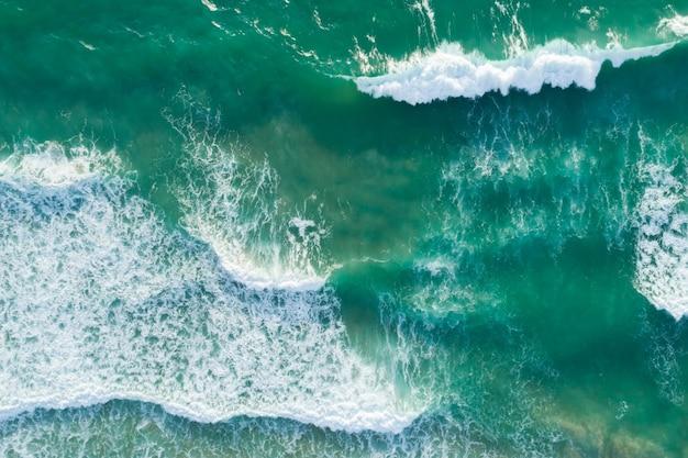 Vista superior das ondas da textura do mar espuma e espirrar no oceano fundo da superfície do mar lindo dia ensolarado.