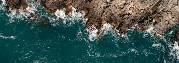 Vista superior das ondas do mar batendo nas rochas
